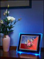 LCD photoframe on polished wood surface adjacent to vase of flowers.