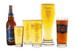 Five filled branded beer glases alongside a bottle of Tiger lager.