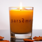 Parseme Candle on reflective surface with petals.