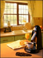 Coffee maker on table with coffee beans and orange juice set in kitchen environment.